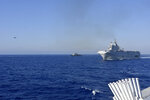This photo provided Friday Aug.14, 2020 by the French Defense Ministry shows the French Tonnerre helicopter carrier, right, escorted by Greek and French military vessels during a maritime exercise in the Eastern Mediterranean, Thursday, Aug. 13, 2020. Greece's prime minister warmly thanked France Thursday for boosting its military presence in the eastern Mediterranean, where Greek and Turkish warships are closely shadowing each other over a Turkish energy exploration bid in waters Athens claims as its own. (French Defense Ministry via AP)