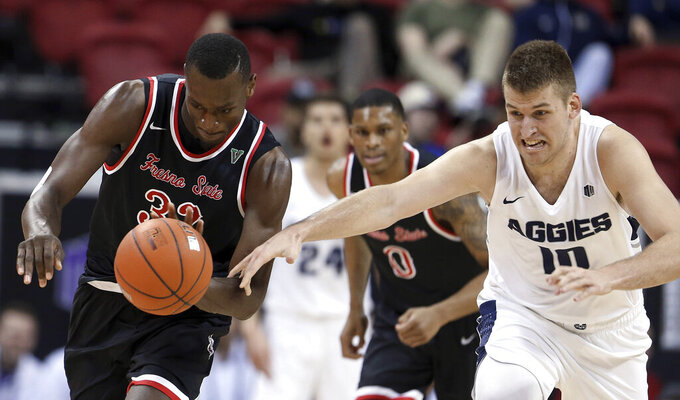 Fresno State's Nate Grimes (32) and Utah State's Quinn Taylor reach for the ball during the second half of an NCAA college basketball game in the Mountain West Conference men's tournament Friday, March 15, 2019, in Las Vegas. (AP Photo/Isaac Brekken)