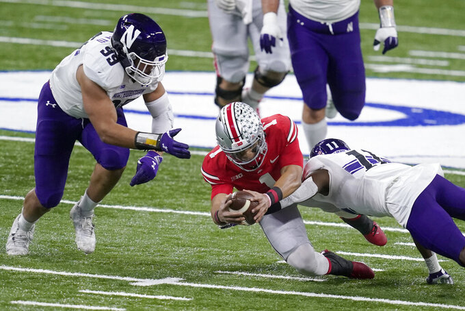 Ohio State quarterback Justin Fields (1) dives for yardage as Northwestern defensive end Earnest Brown IV (99) and defensive back A.J. Hampton (11) defend during the first half of the Big Ten championship NCAA college football game, Saturday, Dec. 19, 2020, in Indianapolis. (AP Photo/Darron Cummings)