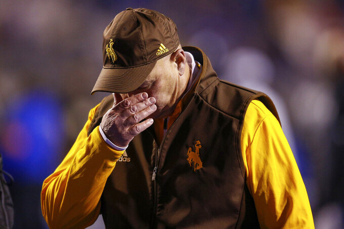 Wyoming head coach Craig Bohl walks off field after falling to the Boise State in overtime of an NCAA college football game Saturday, Nov. 9, 2019, in Boise, Idaho. Boise State won 20-17. (AP Photo/Steve Conner)