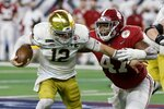 Notre Dame quarterback Ian Book (12) is sacked by Alabama defensive lineman Byron Young (47) in the second half of the Rose Bowl NCAA college football game in Arlington, Texas, Friday, Jan. 1, 2021. (AP Photo/Michael Ainsworth)