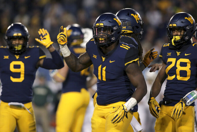 West Virginia linebacker David Long Jr. (11) celebrates wit his teammates after sacking Baylor's quarterback during the first half of an NCAA college football game Thursday, Oct. 25, 2018, in Morgantown, W.Va. (AP Photo/Raymond Thompson)