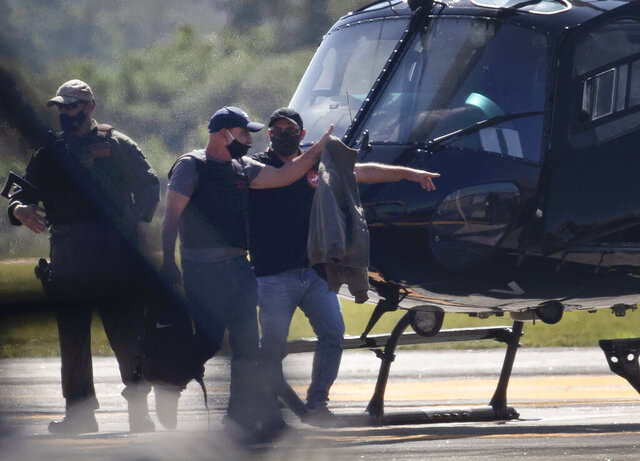 Fabricio Queiroz, second left, is escorted by police after arriving from Sao Paulo at the Japarecagua airport, in Rio de Janeiro, Brazil, Thursday, June 18, 2020. Brazilian authorities on Thursday arrested Queiroz sought as part of an investigation into allegedly suspicious movements of money he made while a driver for Flavio Bolsonaro, a Brazilian senator and son of President Jair Bolsonaro. (AP Photo/Silvia Izquierdo)
