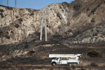 FILE - In this Oct. 15, 2019, file photo, SoCal Edison trucks arrive at the site of a transformer tower in Sylmar, Calif., suspected of being responsible for starting the Saddleridge fire. Fire danger remains high as dry, warm winds blow through Southern California. The National Weather Service says gusts on Sunday, Oct. 20, could top 60 mph (97 kph) in some parts of Los Angeles, Ventura and Santa Barbara counties. Southern California Edison says it's monitoring conditions to determine whether preventive power shut-offs will be needed. (AP Photo/Christian Monterrosa, File)