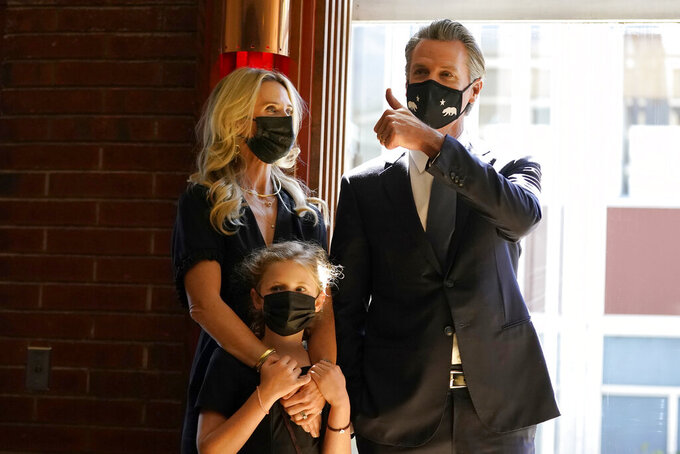 Gov. Gavin Newsom, right, gestures next to his wife, first partner Jennifer Siebel Newsom, and their daughter, Brooklynn, before speaking to volunteers in San Francisco, Tuesday, Sept. 14, 2021. The recall election that could remove California Democratic Gov. Newsom is coming to an end. Voting concludes Tuesday in the rare, late-summer election that has emerged as a national battlefront on issues from COVID-19 restrictions to climate change. (AP Photo/Jeff Chiu)