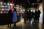FILE - In this Friday, Dec. 20, 2019, photo, people visit the Pulitzer Prize Photography exhibition at the Newseum, in Washington. The Newseum will close the Pennsylvania Avenue location on Dec. 31, 2019. It attracted millions of visitors but lacked a solid financial plan to stay afloat. The mission of the Newseum is to increase public understanding of the importance of a free press and the First Amendment. (AP Photo/Jacquelyn Martin)