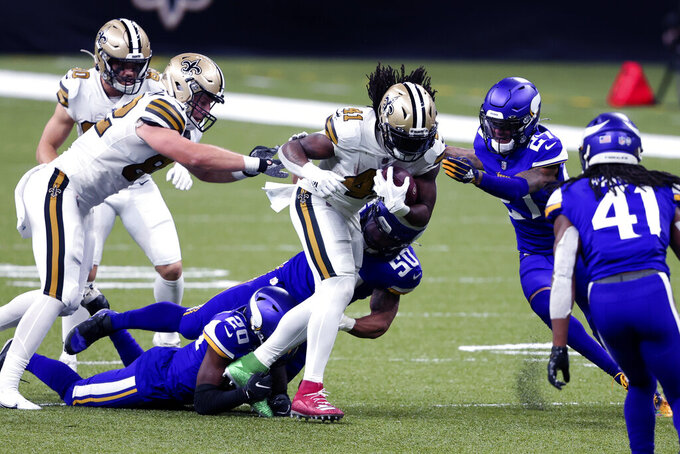 New Orleans Saints running back Alvin Kamara (41) carries against Minnesota Vikings cornerback Jeff Gladney (20) and cornerback Cameron Dantzler (27) in the first half of an NFL football game in New Orleans, Friday, Dec. 25, 2020. (AP Photo/Butch Dill)