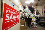 In this Wednesday, Oct. 23, 2019 photo, Merle Adler, a campaign volunteer for Seattle City Council candidate Kshama Sawant, unfurls a string of mailings he received at home in support of challenger Egan Orion, at the campaign office in Seattle. Adler brought the mailings to show Sawant campaign workers how much money and effort is going into the campaign of Orion. Seven of the nine Seattle City Council seats are up for grabs in next month's election, where retail giant Amazon has made unprecedented donations totaling $1.5 million to a political action committee that's supporting a slate of candidates perceived to be friendlier to business. Among the company's top targets is Sawant, a fierce critic of Amazon, who is running against Orion in the District 3 race.  (AP Photo/Elaine Thompson)