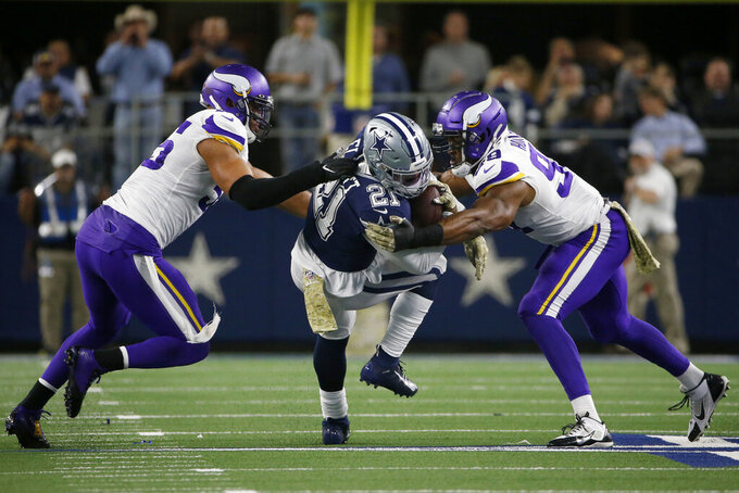 Minnesota Vikings' Anthony Barr, left, and Danielle Hunter (99) combine to stop Dallas Cowboys running back Ezekiel Elliott (21) during the first half of an NFL football game in Arlington, Texas, Sunday, Nov. 10, 2019. (AP Photo/Ron Jenkins)