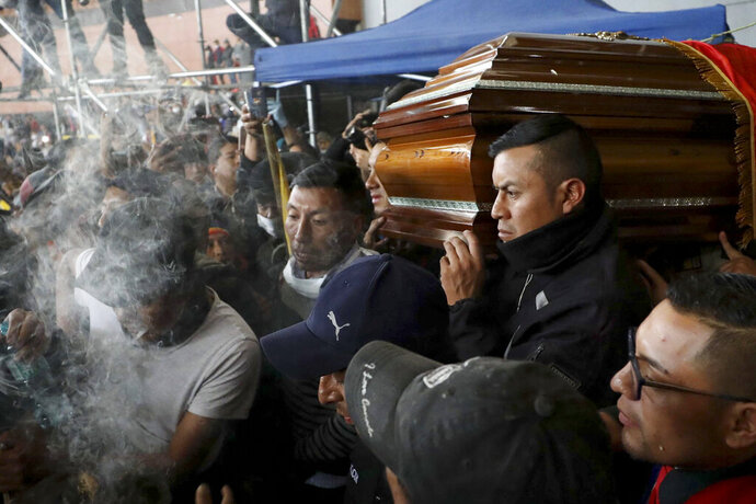 Police held captive by anti-government protesters, are forced to carry a coffin that contains the remains of a companion demonstrator who protesters say died during yesterday's national strike, in a procession inside the Casa de Cultura in Quito, Ecuador, Thursday, Oct. 10, 2019. An indigenous leader and four other people have died in unrest in Ecuador since last week, the public defender's office said Thursday. (AP Photo/Fernando Vergara)