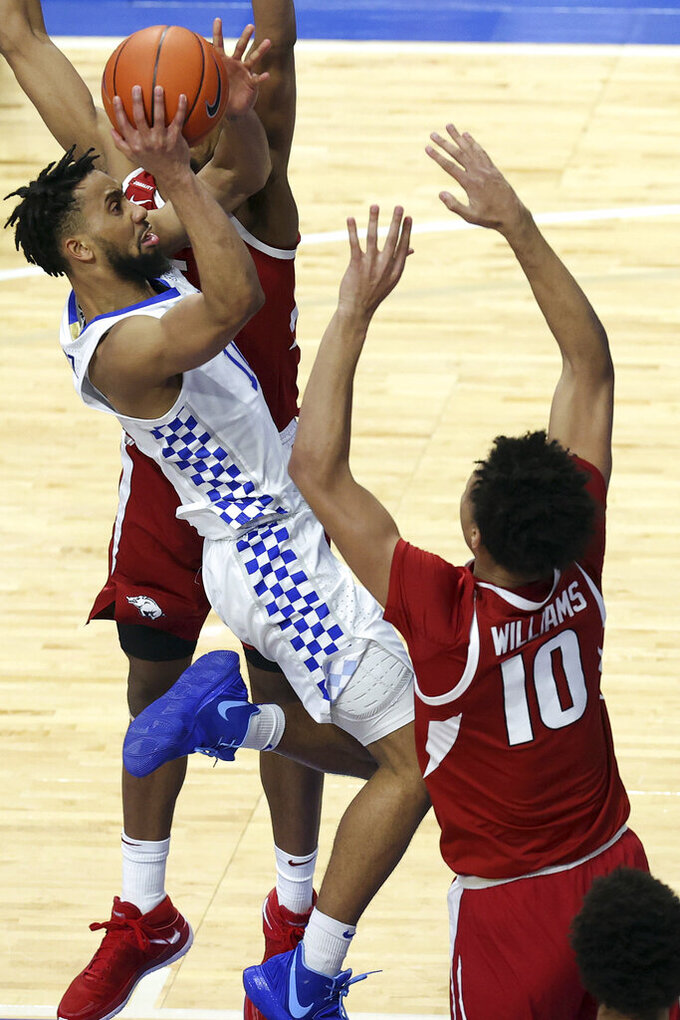 Kentucky's Davion Mintz, left, shoots while defended by Arkansas' Jaylin Williams (10) during the second half of an NCAA college basketball game in Lexington, Ky., Tuesday, Feb. 9, 2021. (AP Photo/James Crisp)