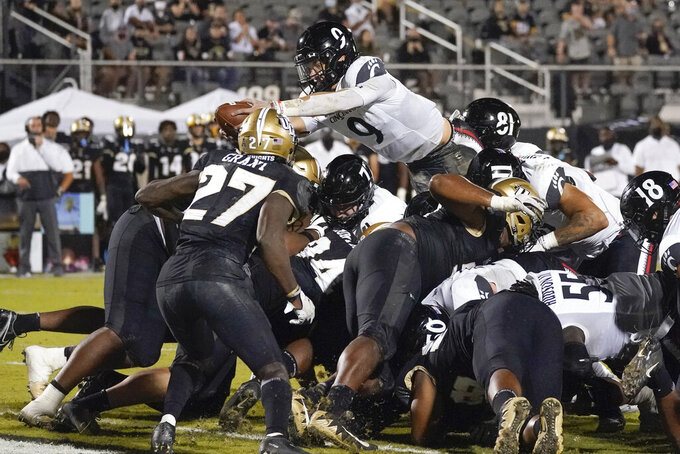 Cincinnati quarterback Desmond Ridder, top center, leaps over the Central Florida defensive line for a 1-yard touchdown during the second half of an NCAA college football game, Saturday, Nov. 21, 2020, in Orlando, Fla. (AP Photo/John Raoux)