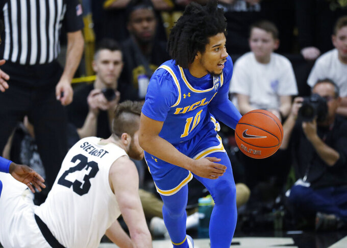 UCLA guard Tyger Campbell, right, picks up the ball after it was turned over by Colorado forward Lucas Siewert in the first half of an NCAA college basketball game Saturday, Feb. 22, 2020, in Boulder, Colo. (AP Photo/David Zalubowski)
