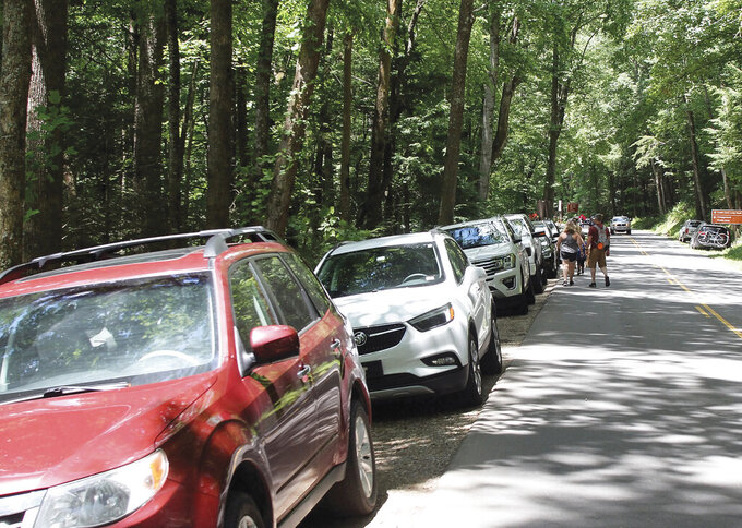 FILE - In this June 24, 2020 file photo, visitors walk down Laurel Creek Road to Cades Cove after parking along the road because parking lots around the Cove were full,  in The Great Smoky Mountains National Park, in Tenn. The outdoors has offered comfort and escape for many Southerners this year. The sudden isolation of being cut off from family, co-workers, and friends during the pandemic has driven more people to nature as an escape from the confines of the living room. (Tom Sherlin/The Daily Times via AP)