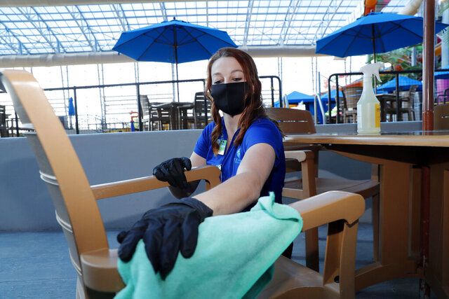 Amid concerns of the spread of COVID-19, Jordyn Kiedas wipes down a chair at the city owned waterpark in Grand Prairie, Texas, Friday, May 29, 2020. (AP Photo/LM Otero)
