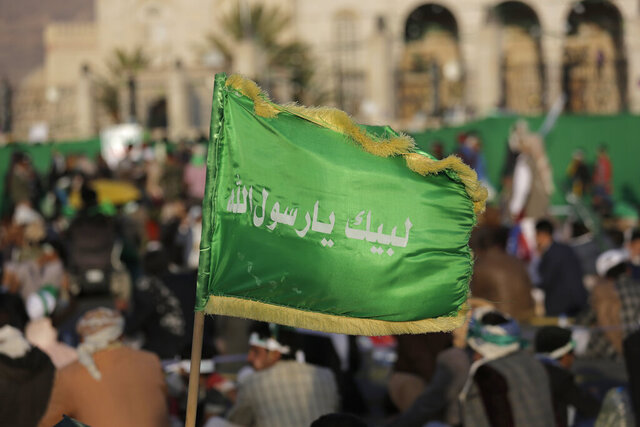FILE - In this Nov. 9, 2019 file photo, a supporter of Shiite rebels, known as Houthis, holds a banner with Arabic writing that reads,