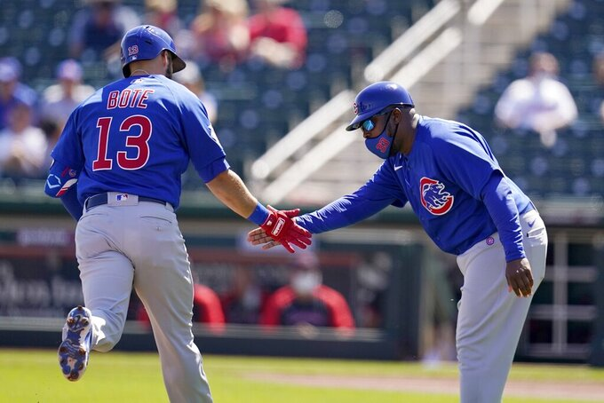 Chicago Cubs' David Bote (13) celebrates his home run against the Cleveland Indians with Cubs third base coach Willie Harris during the first inning of a spring training baseball game Thursday, March 18, 2021, in Goodyear, Ariz. (AP Photo/Ross D. Franklin)