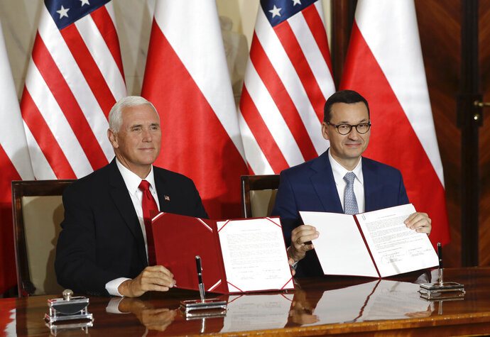 U.S. Vice President Mike Pence and Polish Prime Minister Mateusz Morawiecki display an agreement they signed in Warsaw, Poland, Monday, Sept. 2, 2019. The U.S. and Poland signed an agreement on Monday to cooperate on new 5G technology amid growing concerns about Chinese telecommunications giant Huawei. (AP Photo/Petr David Josek)