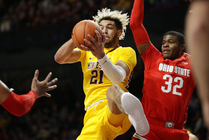 Minnesota forward Jarvis Omersa (21) grabs a rebound in front of Ohio State guard E.J. Liddell (32) in the first half of an NCAA college basketball game Sunday, Dec. 15, 2019, in Minneapolis. (AP Photo/Andy Clayton-King)