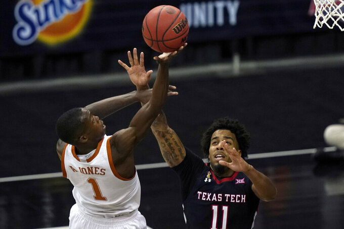 Texas guard Andrew Jones (1) shoots over Texas Tech guard Kyler Edwards (11) during the second half of an NCAA college basketball game in the quarterfinal round of the Big 12 men's tournament in Kansas City, Mo., Thursday, March 11, 2021. Texas defeated Texas Tech 67-66. (AP Photo/Orlin Wagner)