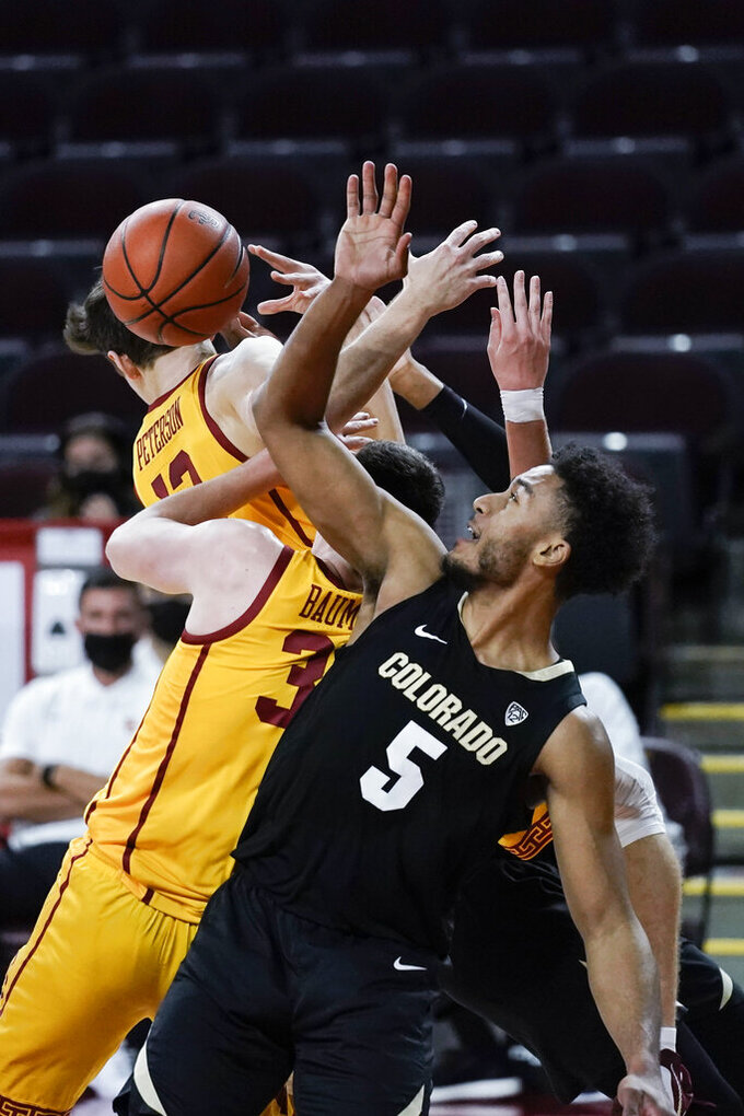 Colorado's D'Shawn Schwartz, front, vies for a rebound with Southern California's Drew Peterson, top left, and Noah Baumann during the first half of an NCAA college basketball game Thursday, Dec. 31, 2020, in Los Angeles. (AP Photo/Jae C. Hong)