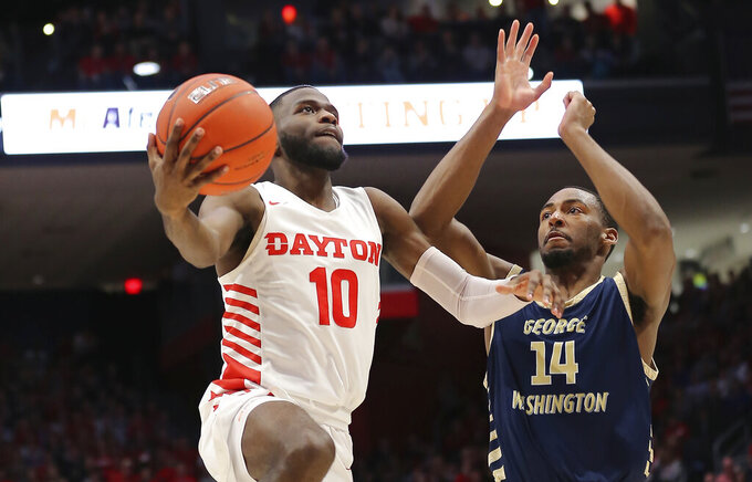 Dayton's Jalen Crutcher (10) drives to the basket against George Washington's Maceo Jack (14) during the second half of an NCAA college basketball game Saturday, March 7, 2020, in Dayton, Ohio. (AP Photo/Tony Tribble)