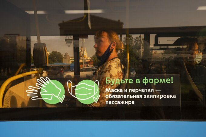 """A woman is seen through a glass window with the words reading """"Keep fit! Mask and gloves are compulsory equipment of passengers"""" inside a bus in Moscow, Russia, Tuesday, June 22, 2021. An ambitious plan of vaccinating 30 million Russians by mid-June against the coronavirus has fallen short by a third, and the country has started to see a surge in daily new infections. So now, many regional governments across the vast country are obligating some workers to get vaccinated and requiring the shots to enter certain businesses, like restaurants. (AP Photo/Pavel Golovkin)"""