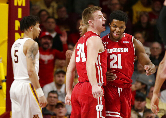 Wisconsin guard Brad Davison (34) yells to forward Kahlil Iverson after Iverson dunked and was fouled, while Minnesota guard Amir Coffey (5) stands nearby, during the first half of an NCAA college basketball game Wednesday, Feb. 6, 2019, in Minneapolis. (AP Photo/Andy Clayton-King)