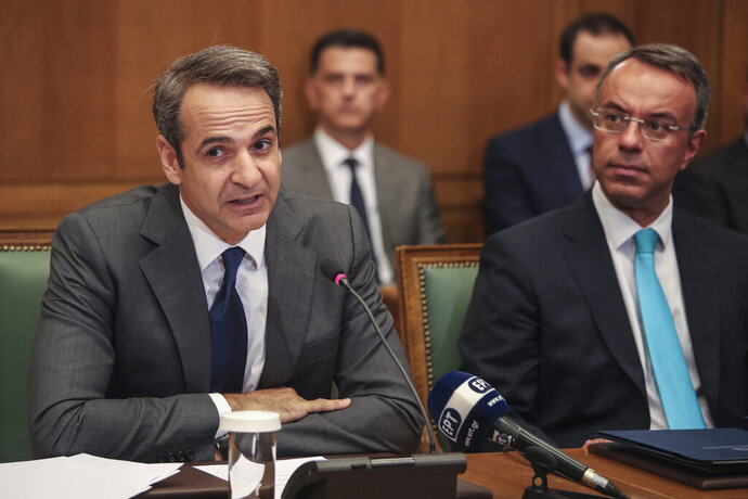 Greek Prime Ministers Kyriakos Mitsotakis, left, speaks next to Finance Minister Christos Staikouras, as new government participate in a first cabinet meeting, in Athens, Wednesday, July 10, 2019. Conservative party leader Kyriakos Mitsotakis won Sunday's election on pledges that included making the country more businesses-friendly, cutting taxes and negotiating an easing of draconian budget conditions agreed as part of the country's rescue program. (AP Photo/Petros Giannakouris)