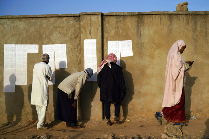 Nigerians check voters' lists at a polling station in Kaduna, Nigeria, Saturday, Feb. 16, 2019. Nigeria's electoral commission delayed the presidential election until Feb. 23, making the announcement a mere five hours before polls were set to open. (AP Photo/Jerome Delay)