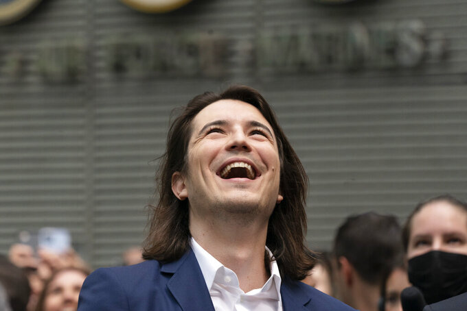 Vladimir Tenev, CEO and Co-Founder of Robinhood, celebrates in New York's Times Square following his company's IPO, Thursday, July 29, 2021. Robinhood is selling its own stock on Wall Street, the very place the online brokerage has rattled with its stated goal of democratizing finance. Through its app, Robinhood has introduced millions to investing and reshaped the brokerage industry, all while racking up a long list of controversies in less than eight years. (AP Photo/Mark Lennihan)
