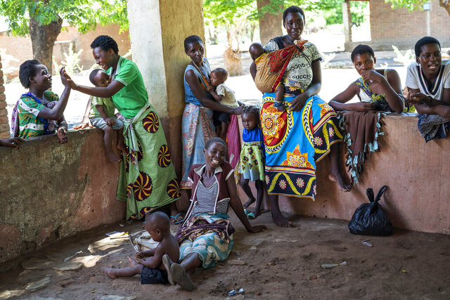 In this photo taken Wednesday, Dec. 11, 2019, residents of the Malawi village of Tomali wait to have their young children become test subjects for the world's first vaccine against malaria. Babies in three African nations are getting the first and only vaccine for malaria in a pilot program. World health officials want to see how well the vaccine works in Malawi, Ghana and Kenya before recommending its wider use.(AP Photo/Jerome Delay)