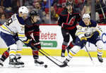 Buffalo Sabres' Jason Pominville (29) reaches for the puck with Carolina Hurricanes' Teuvo Teravainen, of Finland, and Sabres' Jeff Skinner (53) during the first period of an NHL hockey game in Raleigh, N.C., Friday, Jan. 11, 2019. (AP Photo/Gerry Broome)