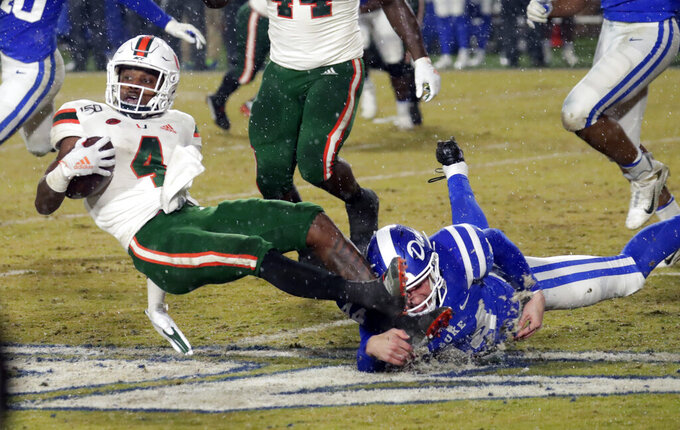 Miami's Jeff Thomas (4) gets tripped up by Duke's Charlie Ham (44) during the fourth quarter of an NCAA college football game in Durham, N.C., Saturday, Nov. 30, 2019. (AP Photo/Chris Seward)