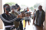 In this Aug. 21, 2021, image taken from video, firearms instructor Wayne Thomas instructs women the proper stance in firearms shooting at the Recoil Firearms store in Taylor, Mich. About 1,000 or so mostly Black women taking part in free weekend gun safety and shooting lessons at two Detroit-area ranges. Black women are increasingly are considering gun ownership for personal protection, according to industry experts and gun rights advocates. (AP Photo/Carlos Osorio)