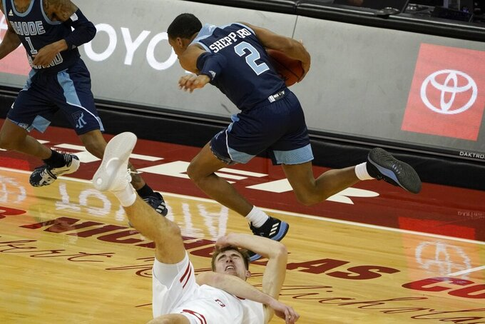 Rhode Island's Jeremy Sheppard jumps over Wisconsin's Tyler Wahl during the second half of an NCAA college basketball game Wednesday, Dec. 9, 2020, in Madison, Wis. (AP Photo/Morry Gash)