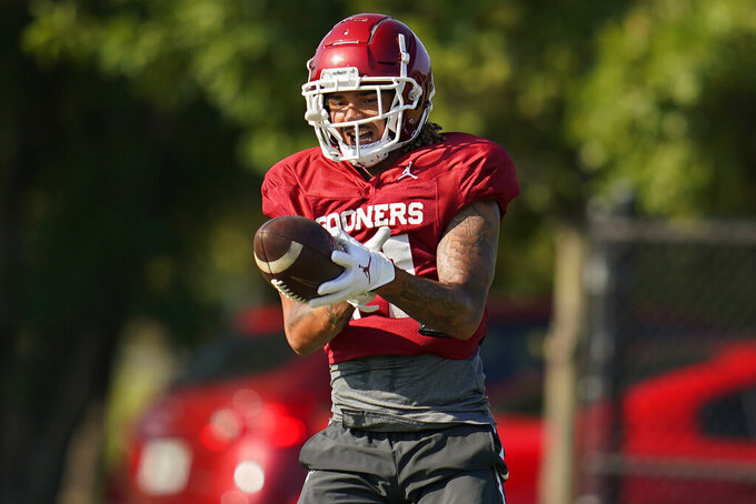 Oklahoma wide receiver Jadon Haselwood catches a pass during an NCAA college football practice, Tuesday, Aug. 10, 2021, in Norman, Okla. (AP Photo/Sue Ogrocki)