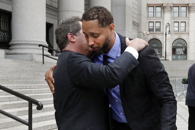 Former assistant basketball coach for the University of Southern California Tony Bland, right, is embraced by his attorney Jeffrey Lichtman as they leave federal court in New York, Wednesday, June 5, 2019. Bland was the first of four ex-coaches charged with crimes to plead guilty to bribery conspiracy. He was sentenced to 100 hours of community service and two years of probation. (AP Photo/Richard Drew)