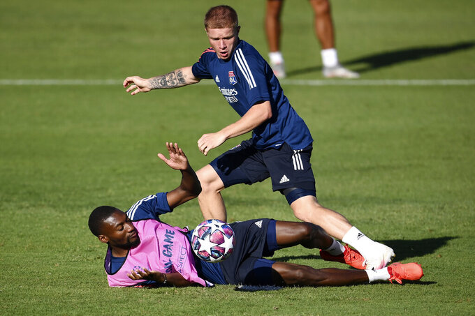 Lyon's Melvin Bard vies for the ball with teammate Karl Toko Ekambi, on the ground, during a training session at the Restelo stadium in Lisbon, Tuesday Aug. 18, 2020. Lyon will play Bayern in a Champions League semifinals soccer match on Wednesday. (Franck Fife/Pool via AP)