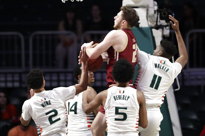 Boston College forward Nik Popovic (21) goes to the basket as Miami guard Isaiah Wong (2), guard Harlond Beverly (5) and forward Anthony Walker (11) defend during the second half of an NCAA college basketball game, Wednesday, Feb. 12, 2020, in Coral Gables, Fla. Miami won 85-58. (AP Photo/Lynne Sladky)