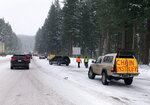 A seasonal business offers chain-up help as motorists put snow chains on their tires Wednesday Nov. 27, 2019 before driving over snowy Santiam Pass, Ore. (AP Photo/Andrew Selsky)