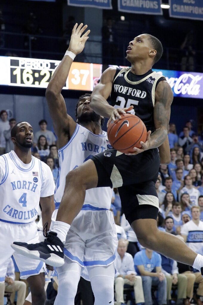 Wofford's Messiah Jones (25) drives against North Carolina's Brandon Huffman (42) during the second half of an NCAA college basketball game in Carmichael Arena in Chapel Hill, N.C., Sunday, Dec. 15, 2019. (AP Photo/Chris Seward)