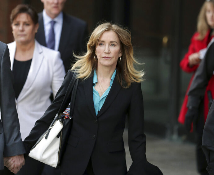 """FILE - This April 3, 2019 file photo shows actress Felicity Huffman departing federal court in Boston after facing charges in a nationwide college admissions bribery scandal. Federal prosecutors are asking a judge to sentence """"Desperate Housewives"""" star Felicity Huffman to a month in jail for her role in the sweeping college admissions bribery scandal. (AP Photos/Charles Krupa, File)"""