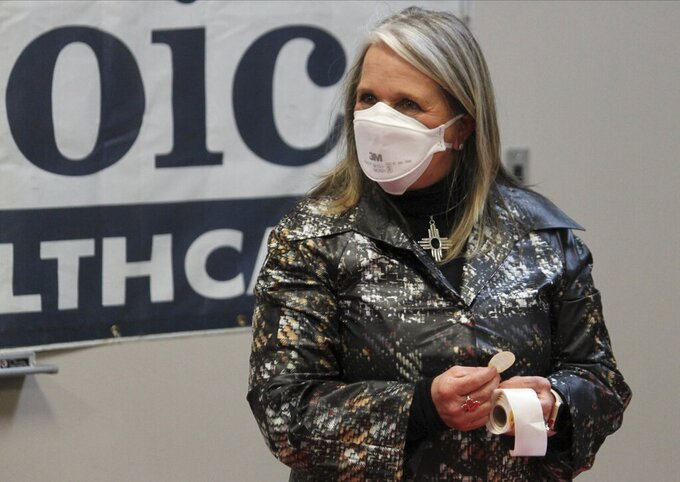 This April 21, 2021 image shows Gov. Michelle Lujan Grisham preparing to hand out stickers to people who just received their COVID-19 vaccinations at a health clinic in Albuquerque, New Mexico. Lujan Grisham on Wednesday, April 28, 2021, announced that the state would reopen and lift its capacity restrictions on restaurants and other businesses when at least 60% of residents 16 and older are fully vaccinated. She said that's expected to happen at the end of June. (AP Photo/Susan Montoya Bryan)