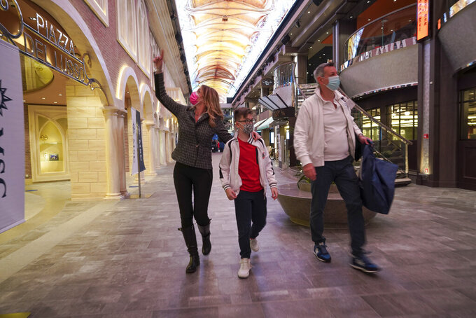 Passengers, Ilaria Gelli, 48, left, Federico Marzocchi, 45, right, and and their son Matteo Marzocchi, 10, walk on board the MSC Grandiosa cruise ship in Civitavecchia, near Rome, Wednesday, March 31, 2021. MSC Grandiosa, the world's only cruise ship to be operating at the moment, left from Genoa on March 30 and stopped in Civitavecchia near Rome to pick up more passengers and then sail toward Naples, Cagliari, and Malta to be back in Genoa on April 6. For most of the winter, the MSC Grandiosa has been a lonely flag-bearer of the global cruise industry stalled by the pandemic, plying the Mediterranean Sea with seven-night cruises along Italy's western coast, its major islands and a stop in Malta. (AP Photo/Andrew Medichini)