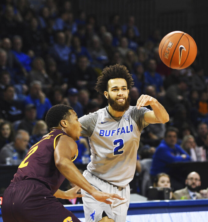 Buffalo's Jeremy Harris, right, passes the ball past Central Michigan's Shawn Roundtree, Jr., during an NCAA college basketball game in Buffalo, N.Y., Saturday, Feb. 9, 2019. (AP Photo/Heather Ainsworth)