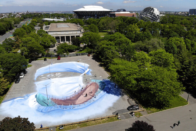 Artist Jorge Rodriguez-Gerada works on a 20,000 square foot mural of a healthcare worker near the Queens Museum, back left, and the USTA Billie Jean King National Tennis Center, back center, in the Queens borough of New York, Wednesday, May 27, 2020. The mural is to honor those who lost their lives during the coronavirus pandemic, especially minority healthcare workers. The portrait was inspired by Dr. Ydelfonso Decoo, an immigrant doctor who died from coronavirus complications while serving hard-hit communities of color. (AP Photo/Seth Wenig)