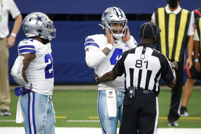 Dallas Cowboys' Ezekiel Elliott (21) looks on as umpire Roy Ellison (81) checks on quarterback Dak Prescott (4) in the second half of an NFL football game against the Atlanta Falcons in Arlington, Texas, Sunday, Sept. 20, 2020. (AP Photo/Michael Ainsworth)