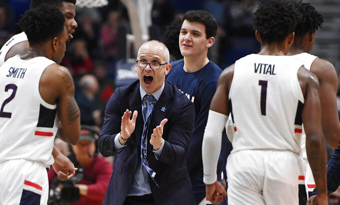 FILE - In this Feb. 14, 2019, file photo, Connecticut head coach Dan Hurley urges his team onduring the first half of an NCAA college basketball game in Hartford, Conn. Hurley is hopeful that recently passed legislation in Connecticut allowing college athletes to profit from the use of their names, images and likenesses will keep more players in school. (AP Photo/Jessica Hill, File)