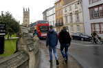 FILE - In this Sept. 3, 2017, file photo, people walk around Oxford University's campus in Oxford, England. Tax and charity records show that prestigious universities around the world, including Oxford, have accepted at least $60 million from the family that owns OxyContin maker Purdue Pharma over the past five years, even as the company has been embroiled in lawsuits over its role in the opioid epidemic. (AP Photo/Caroline Spiezio, File)